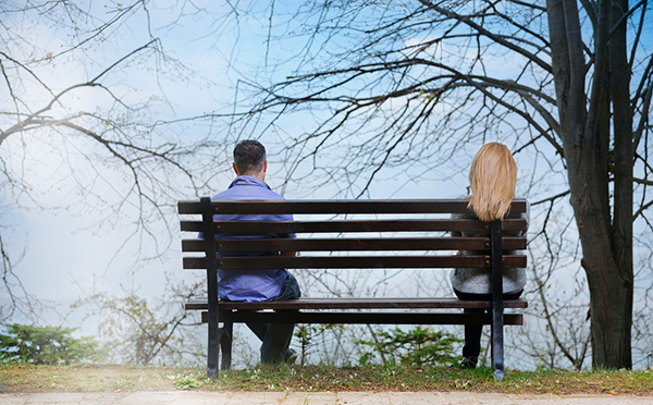 man and woman sitting on opposite sides of a bench