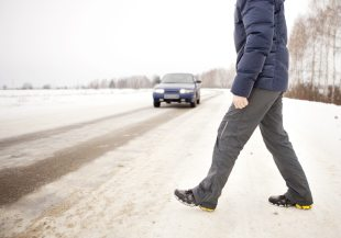man walking across snowy road with car coming towards him