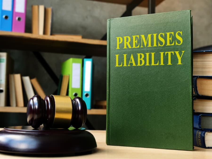 a premises liability book and a gavel laying on a desk