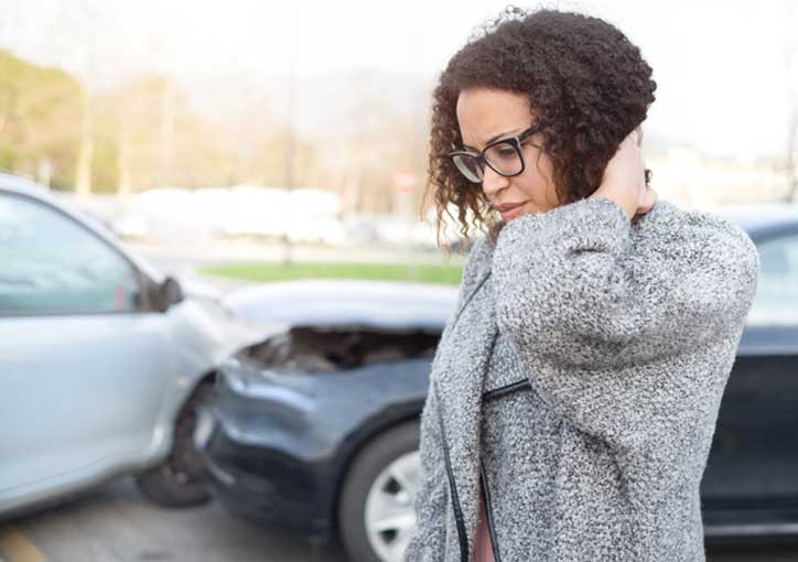 woman rubbing her neck after a car accident