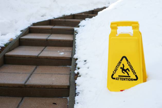 Slippery winter stairs with caution sign