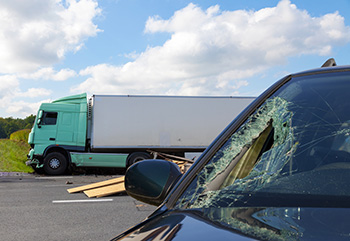 View of a car's smashed windshield with debris on road and a semi truck in background