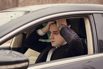 Distressed man sitting in car with hands on forehead