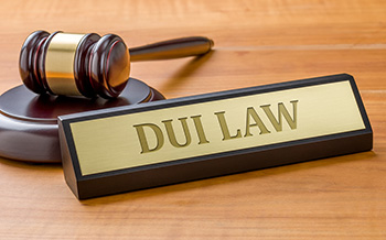 Engraved nameplate that reads DUI near a gavel on a desk
