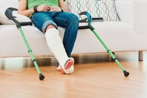 man with cast on right leg sitting on couch with crutches next to him