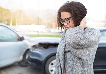 Woman holding her neck walking from a car collision in background