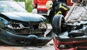 firefighter standing between two heavily damaged cars at an accident scene