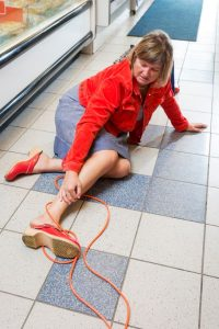 a woman on the floor of a store with a cord around her ankle