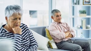 elderly man and woman on opposite ends of a couch looking frustrated