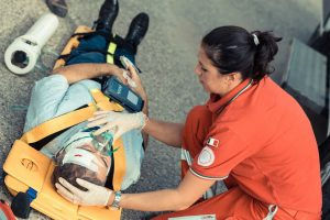 woman emergency technician looking after a man strapped to a stretcher with bandages on his head