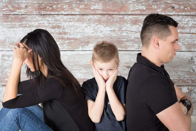 young boy with his head in hands sitting between his parents who aren't facing each other