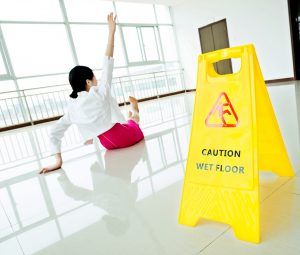 Businesswoman slips and falls on floor near a caution wet floor sign
