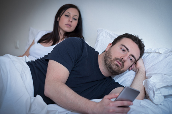 couple in bed, man is turned over looking at phone and woman is trying to see who he's talking to