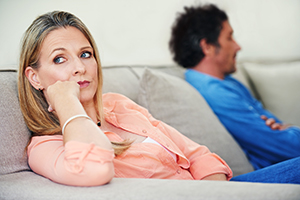 man and woman sitting on opposite ends of couch