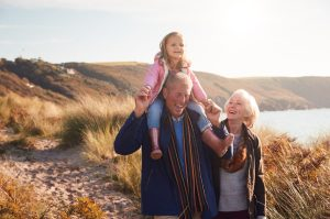 grandparents walking through sand dunes with granddaughter on grandfather's shoulders