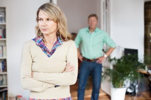 upset older woman standing with older man in the background