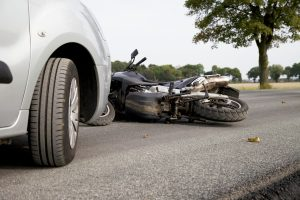 motorcycle laying on road after being hit by car