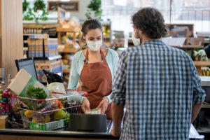 man wearing a protective mask checking out at grocery store