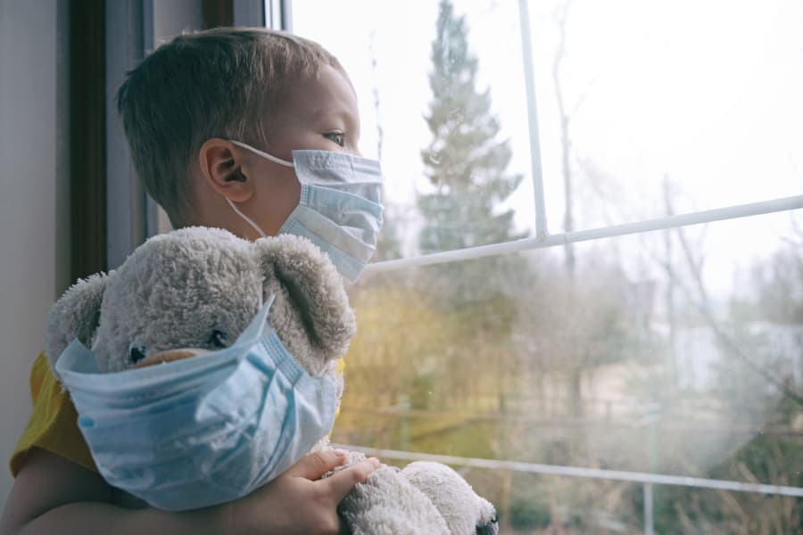 little boy holding his teddy bear looking out the window, both wearing a protective medical mask