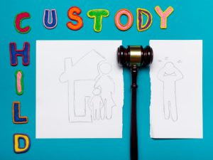 a family drawing torn in half with a judge's gavel in the middle and colorful child custody letters beside and above it