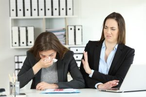 2 businesswomen standing at a desk, one coughing into a tissue and the other leaning away with her left hand up as a shield