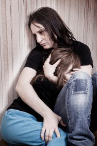 battered woman sitting on the floor holding her young daughter