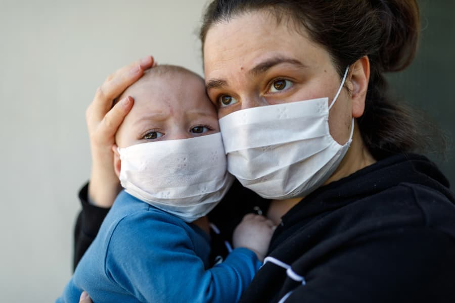 Mother holding baby, both wearing protective masks