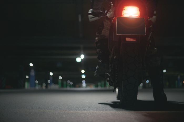 Motorcycle rider sitting on his bike at night in a parking garage