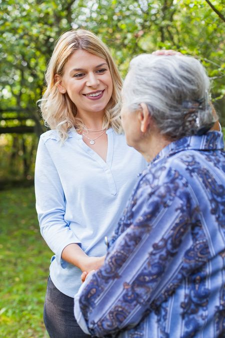 A friendly caregiver walking with a senior woman in a park