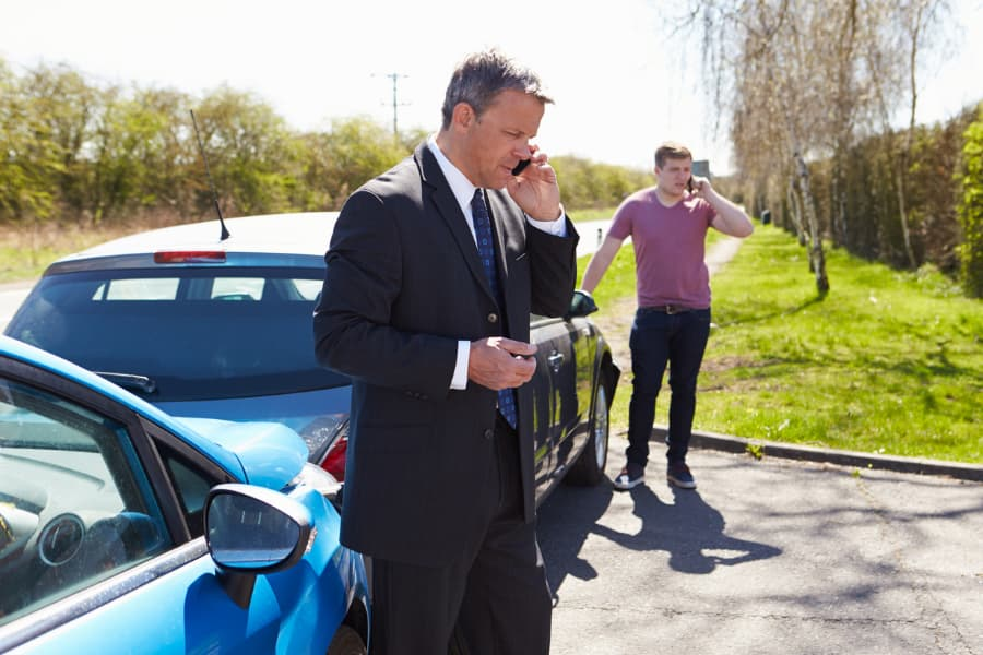 a businessman and young man standing next to a car accident talking on phones