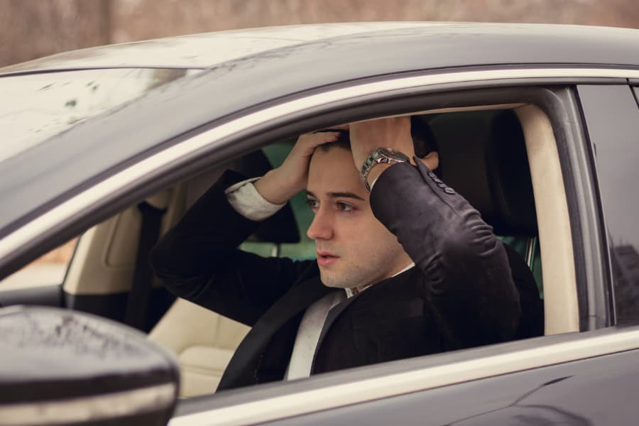 distressed young businessman sitting behind the wheel with hands on head