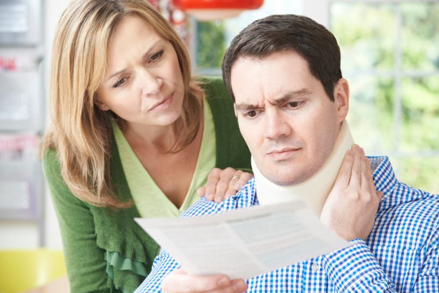 husband in a neck brace looking over a document with wife
