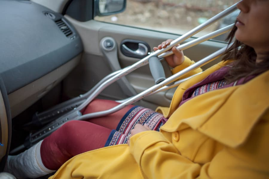 woman holding crutches while sitting in passenger seat with a leg cast