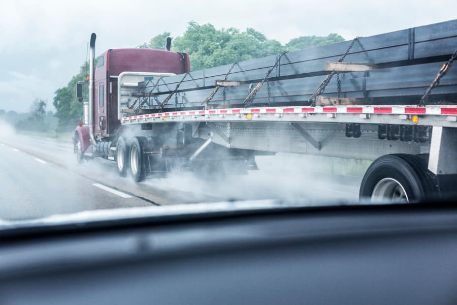 view from a car windshield of an 18-wheeler flatbed trailer truck on a rain-soaked highway