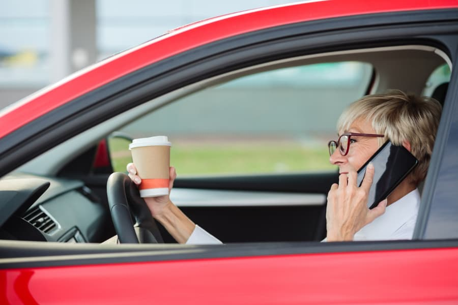 older woman driving car while talking on phone and drinking coffee