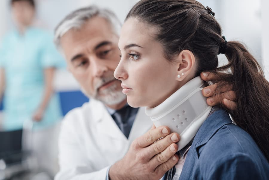 woman being fitted for neck brace after injury