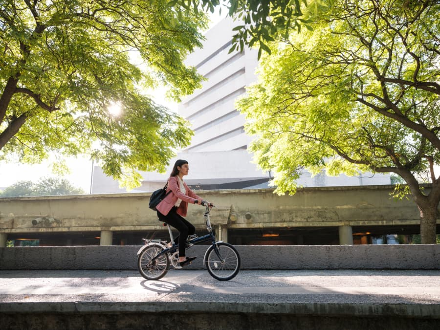 young professional woman riding bike to work