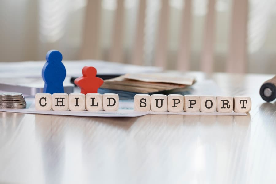 Wooden representation of child and parent behind blocks spelling CHILD SUPPORT