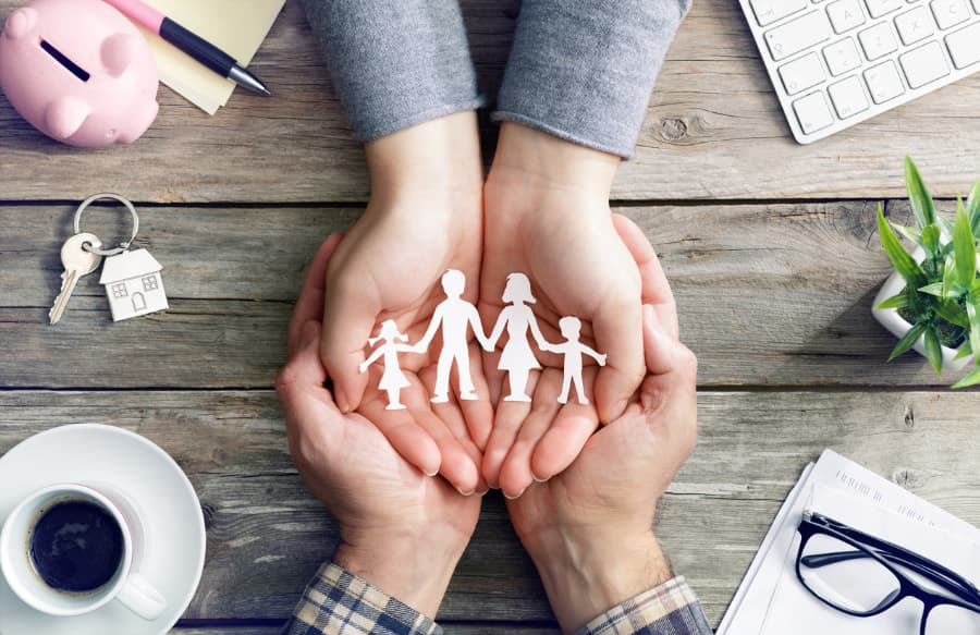 Cupped hands holding cutout of family
